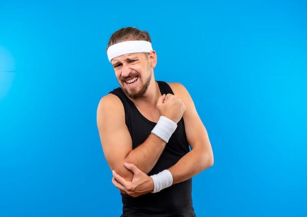 Dolor joven apuesto hombre deportivo con diadema y muñequeras apretando el puño y sosteniendo su codo aislado en la pared azul con espacio de copia