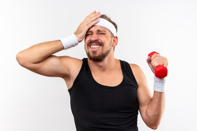 Dolor joven apuesto hombre deportivo con diadema y muñequeras sosteniendo mancuernas y poniendo la mano en la cabeza aislada en la pared blanca