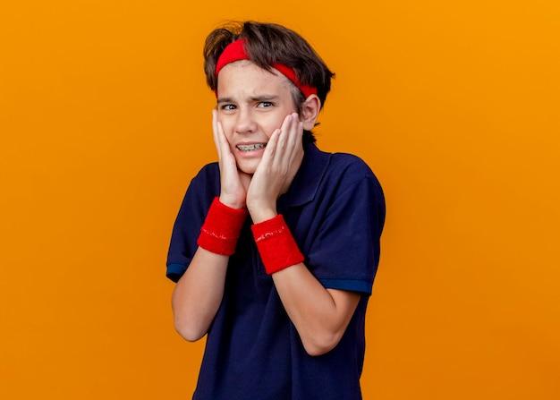 Dolor joven apuesto muchacho deportivo con diadema y muñequeras con aparatos dentales mirando al frente manteniendo las manos en la cara aislada en la pared naranja