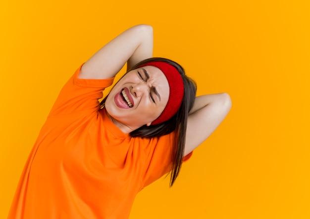 Dolor de joven deportivo vistiendo diadema y muñequeras manteniendo las manos detrás de la espalda haciendo ejercicio con los ojos cerrados