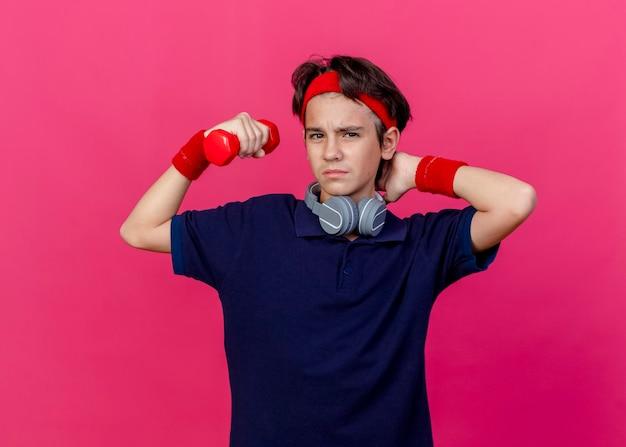 Dolor de joven guapo deportivo con diadema, muñequeras y auriculares en el cuello con aparatos dentales levantando mancuernas manteniendo la mano detrás del cuello mirando al frente aislado en la pared rosa