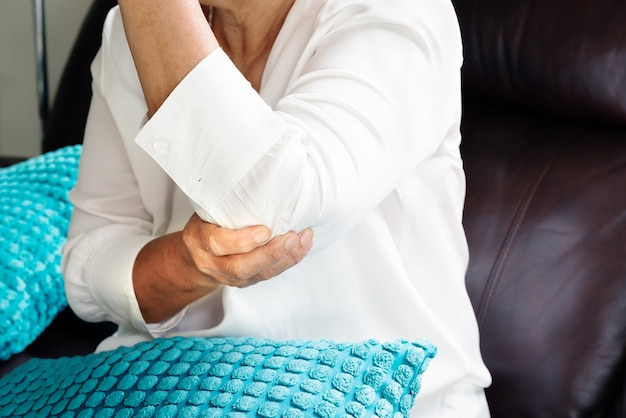 Dolor / lesión en el codo, anciana que sufre de dolor en el codo, concepto de problema de salud