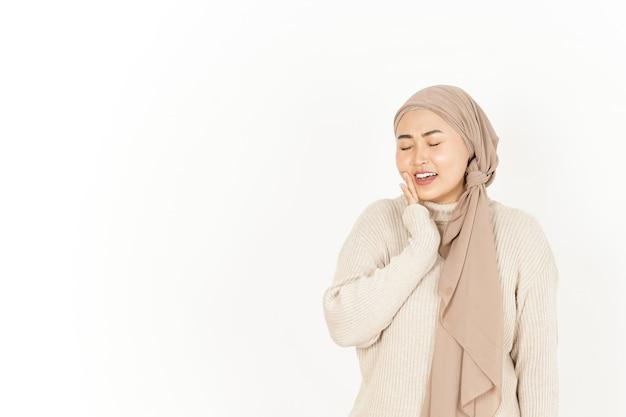 Dolor de muelas con la mano en la mejilla de la hermosa mujer asiática vistiendo hijab aislado sobre fondo blanco.