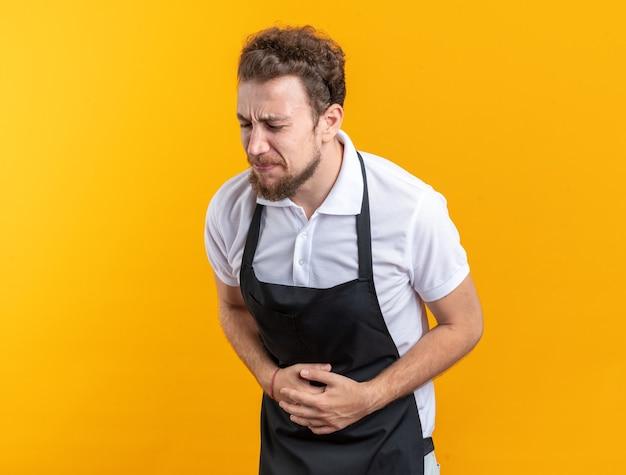 Dolor con los ojos cerrados joven barbero vistiendo uniforme agarró el estómago aislado en la pared amarilla
