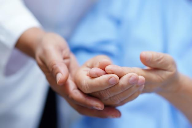 Dolor paciente asiático del gatillo del dolor de la mujer mayor en su mano en hospital.