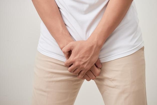 Dolor en la próstata, hombre que sufre de prostatitis o de una enfermedad venérea, foto de estudio sobre fondo blanco.
