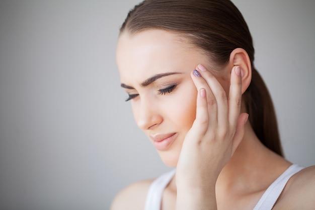 Dolor. retrato de una mujer joven tiene dolor de cabeza