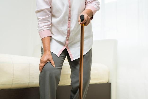 Dolor de rodilla de mujer senior con palo, problema de salud del concepto senior