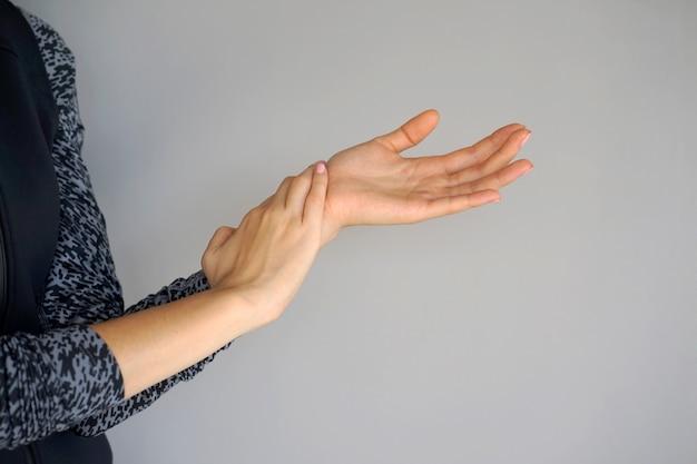 Dolor severo en la mano de una mujer.
