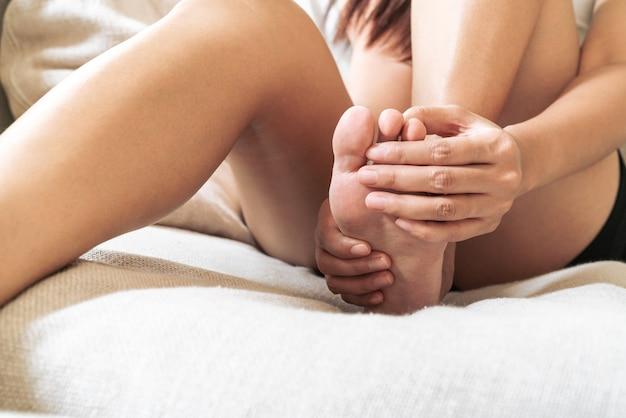 Dolor en el tobillo del pie dolor mujeres tocan su pie doloroso