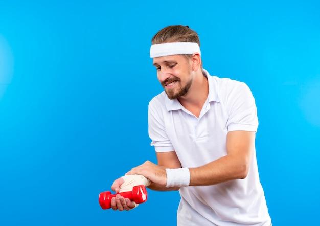 Doloroso joven apuesto deportivo con diadema y muñequeras sosteniendo mancuernas y poniendo la mano en su muñeca lesionada envuelta con vendaje aislado en la pared azul con espacio de copia