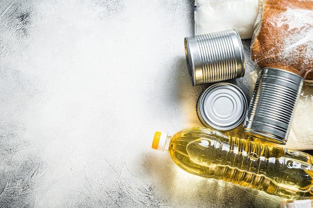 Donación de alimentos, concepto de ayuda de cuarentena. aceite, conservas, pasta, pan, azúcar, huevo. mesa blanca. vista superior. copie el espacio.