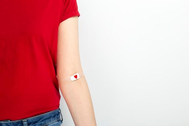 Donación de sangre chica joven en camiseta roja grabada a mano con parche con corazón rojo después de dar sangre sobre fondo gris.