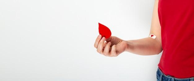 Donación de sangre la chica joven en camiseta roja sostiene la gota en su mano, la segunda mano pegada con el remiendo con el corazón rojo después de dar sangre en fondo gris.
