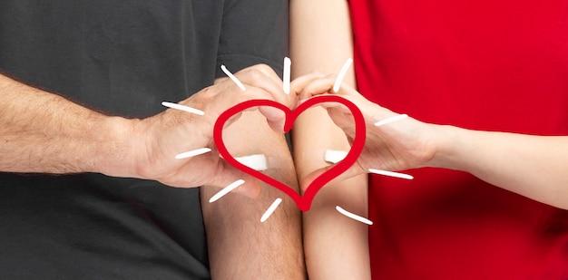 Donación de sangre hombre en gris y mujer en camiseta roja con parche pegado con las manos después de dar sangre, el corazón muestra las manos.
