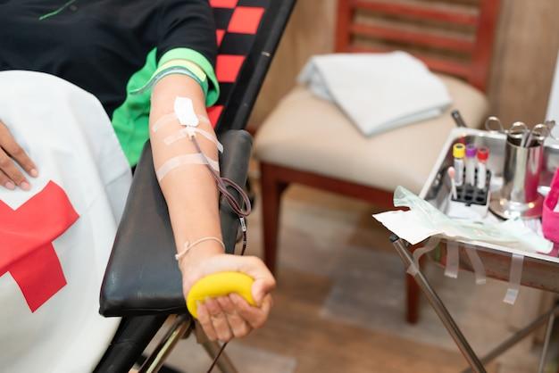 Donante de sangre en la donación con una pelota hinchable sosteniendo en la mano