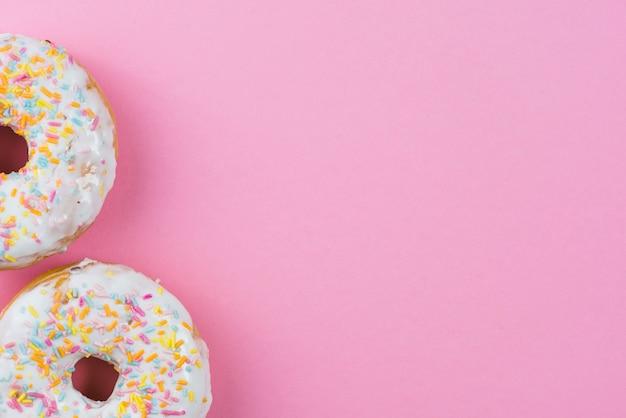 Donas de azúcar con glaseado de chocolate y salpicaduras sobre fondo rosa