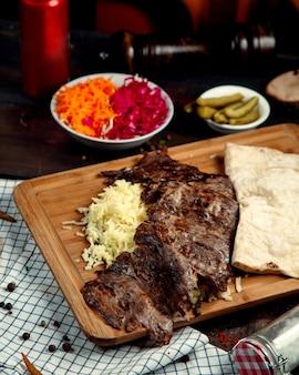 Doner de carne con arroz y lavash sobre tabla de madera