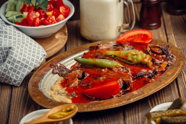 Doner iskender turco en placa de cobre con salsa de tomate y pimiento verde.