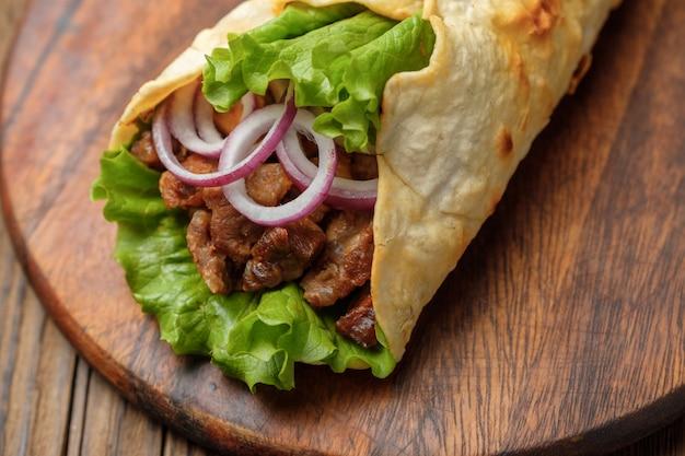 Doner kebab está acostado en la tabla de cortar. shawarma con carne, cebolla, ensalada se encuentra en una vieja mesa de madera blanca.