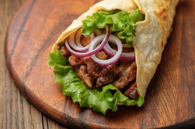 Doner kebab está acostado en la tabla de cortar. shawarma con carne, cebolla, ensalada se encuentra en una vieja mesa de madera oscura.
