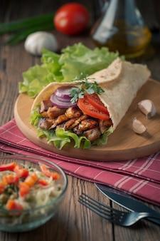 Doner kebab está acostado en la tabla de cortar. shawarma con carne de pollo, cebolla, ensalada se encuentra en una vieja mesa de madera oscura.