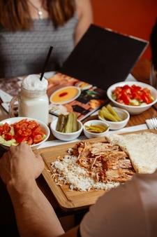 Doner kebab con arroz sobre tabla de madera