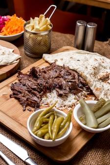 Doner kebab de cordero servido sobre arroz con pan plano y encurtidos