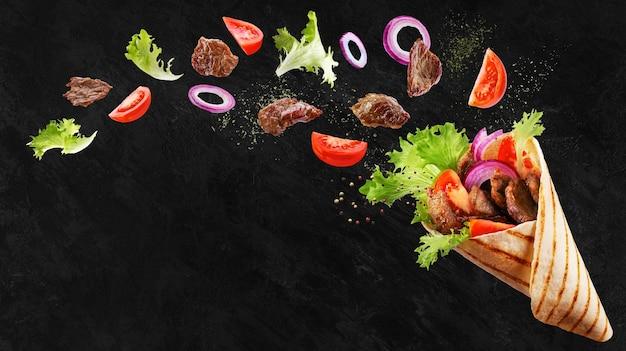 Doner kebab o shawarma con ingredientes flotando en el aire carne de res, lechuga, cebolla, tomate, especias.