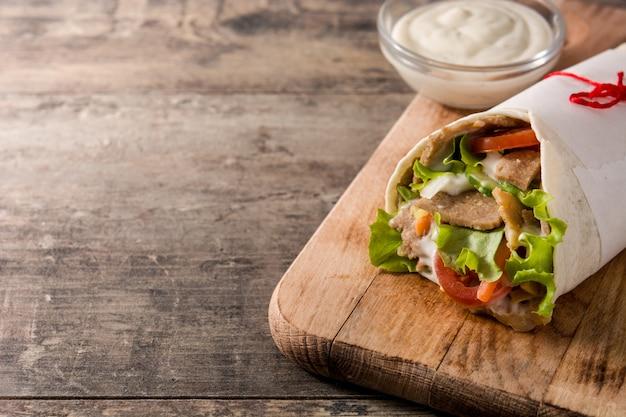 Doner kebab o shawarma sandwich en espacio de copia de mesa de madera