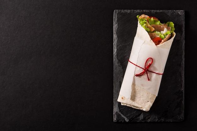 Doner kebab o shawarma sandwich en pizarra negra