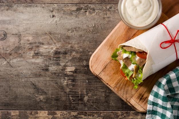 Doner kebab o shawarma sandwich en vista superior de la mesa de madera espacio de copia