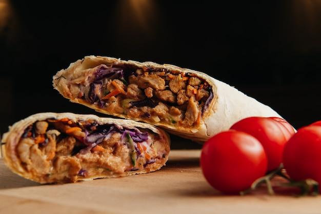 Doner kebab turco con carne a la parrilla. shawarma jugoso en tablero de madera