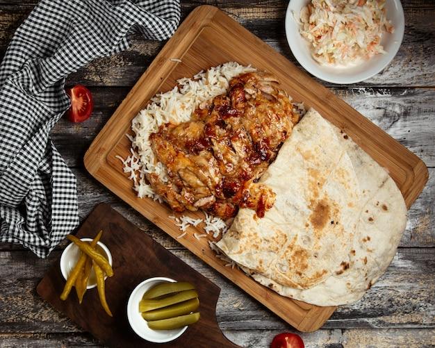 Doner de pollo frito con arroz sobre tabla de madera