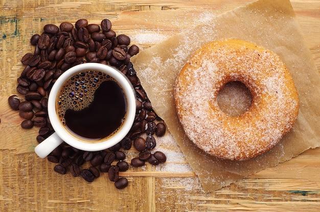 Donut con azúcar y una taza de café caliente en la mesa de madera. vista superior