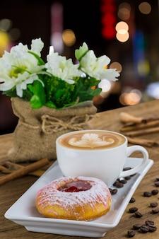 Donut y café con leche en plato blanco sobre mesa de madera