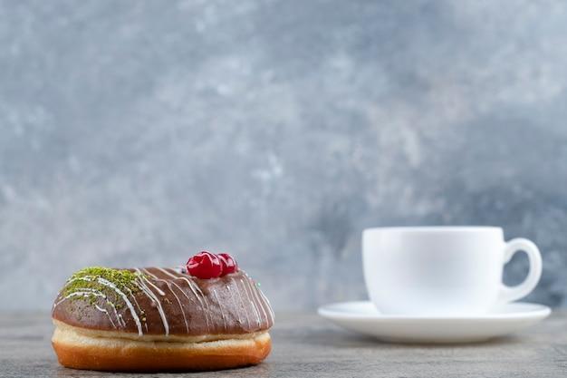 Donut de chocolate con bayas y chispitas y taza de té caliente sobre fondo de piedra.