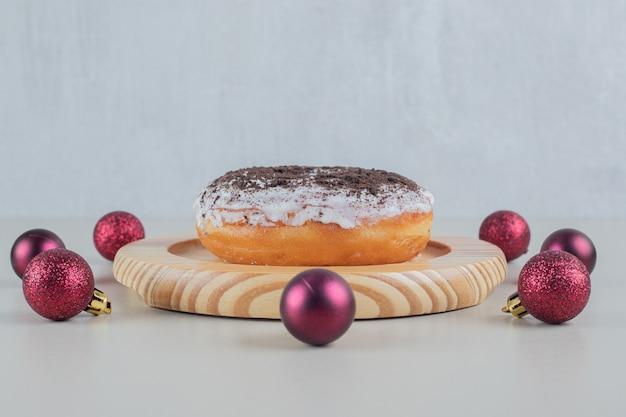 Donut de chocolate con bolas de navidad.