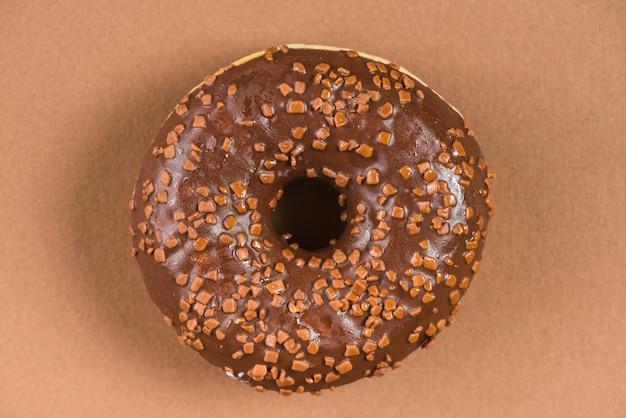 Donut de chocolate oscuro con salpicaduras sobre fondo marrón