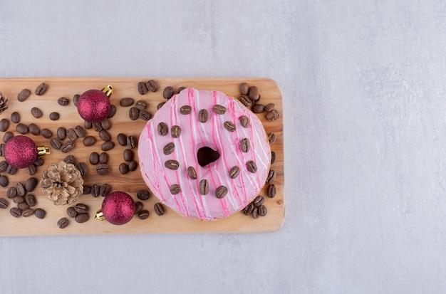 Donut con frijoles de café, granos de café, piñas y adornos navideños sobre fondo blanco.
