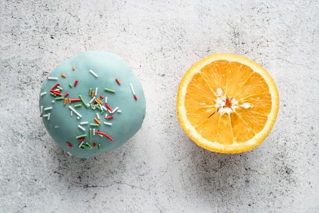 Donut glaseado y naranja a la mitad sobre fondo de hormigón