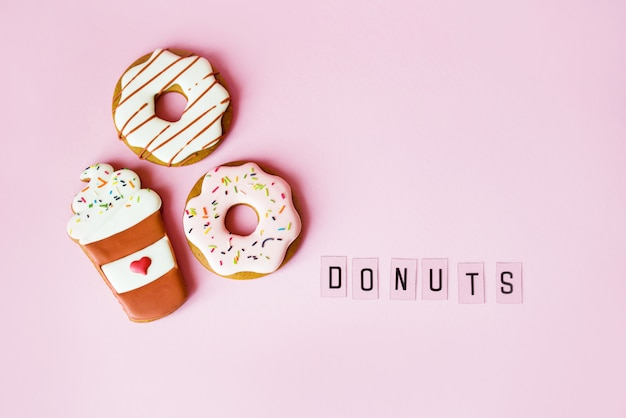 Donut grande y donut de pan de jengibre en la decoración de cumpleaños de superficie rosa
