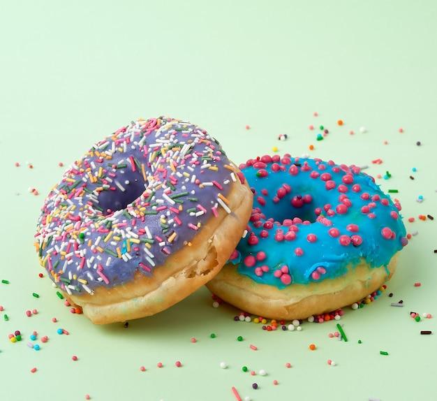 Donut horneado redondo con chispitas de azúcar de colores y glaseado de azúcar azul sobre un fondo verde