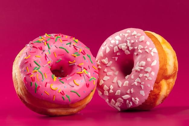Donut redondo glaseado delicioso en una pared rosa brillante
