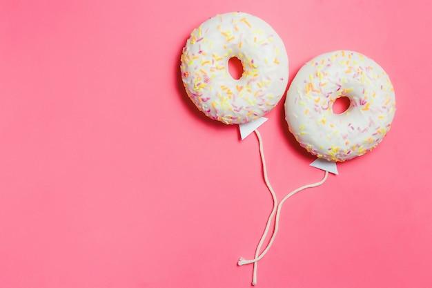 Donut en rosa, fondo de minimalismo creativo de alimentos, donut en forma de globo en el cielo, vista superior con espacio de copia, tonificado