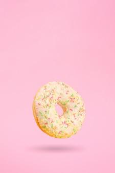 Donut en rosa con sombra colgando en el aire