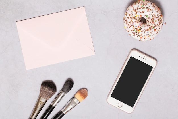 Donut y teléfono inteligente cerca de pinceles y papel