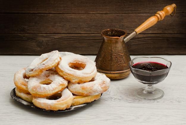 Donuts en azúcar en polvo, cezve de café y mermelada de grosella en una madera