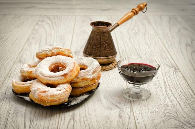 Donuts en azúcar en polvo, cezve de café y mermelada de grosella sobre un fondo de madera