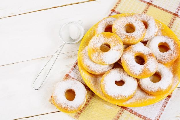 Donuts con azúcar en polvo servido en placa amarilla vista superior copia espacio